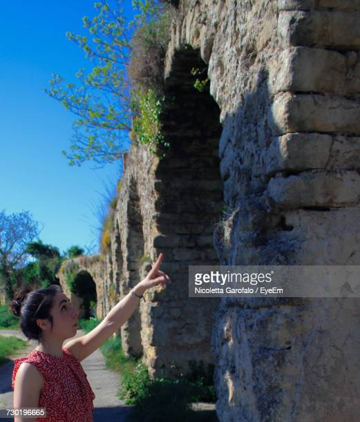 Side View Of Young Woman Pointing At Shadow On Old Brick Wall