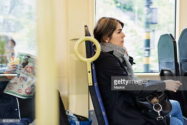 Side view of young woman sitting in tram
