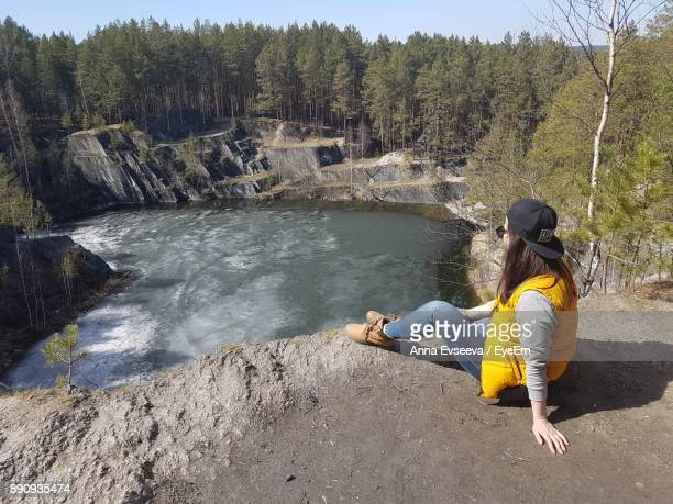 Side View Of Young Woman Sitting On Rock By Lake In Forest