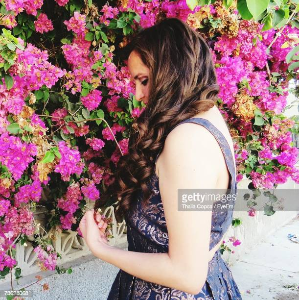 Side View Of Young Woman Standing By Pink Flowers Growing On Plants