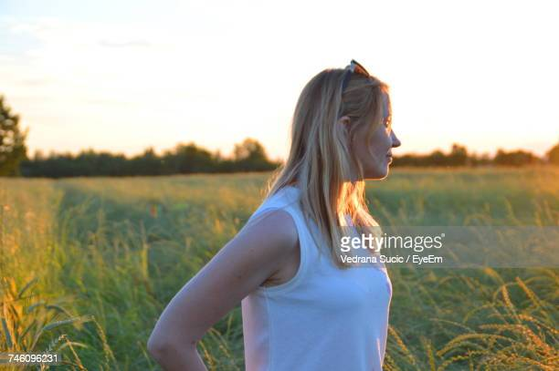Side View Of Young Woman Standing On Field Against Sky During Sunset