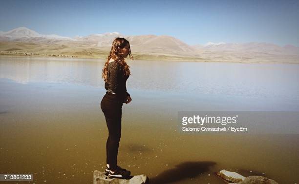 Side View Of Young Woman Standing On Rock In Lake