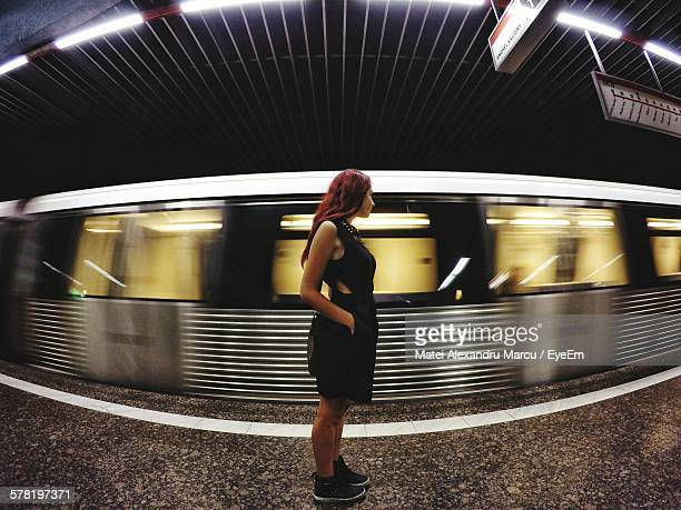 Side View Of Young Woman Standing With Hand In Pocket At Subway Station
