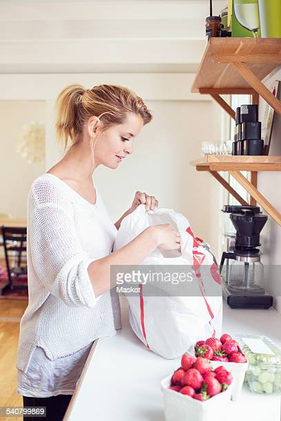 Side view of young woman unpacking fruits from shopping bag at kitchen counter