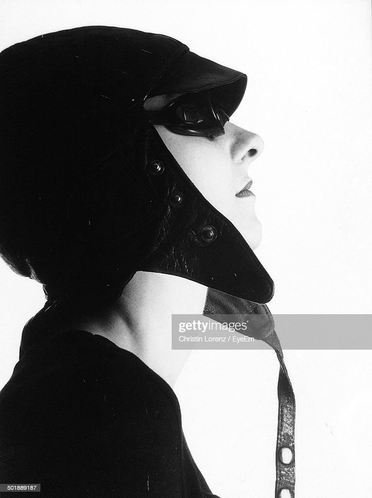Side view of young woman wearing aviator cap and sunglasses