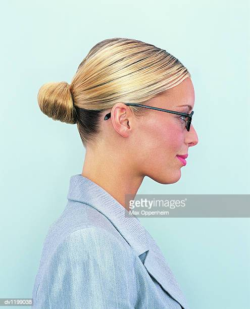 Side View Portrait of a Young Businesswoman With a Hair Bun and Wearing Spectacles