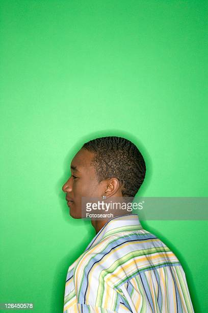 Side view portrait of African-American teen boy against green background.