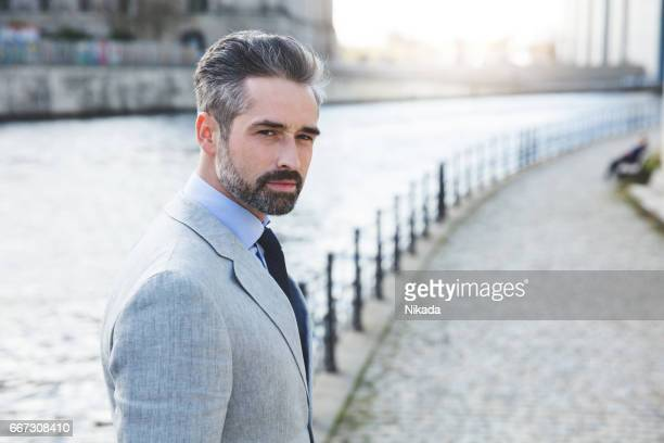 Side view portrait of confident businessman standing on promenade by river