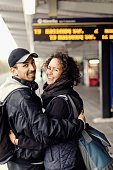 Side view portrait of happy couple with arms around on subway platform