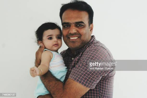 Side View Portrait Of Happy Man Carrying Daughter Against White Background