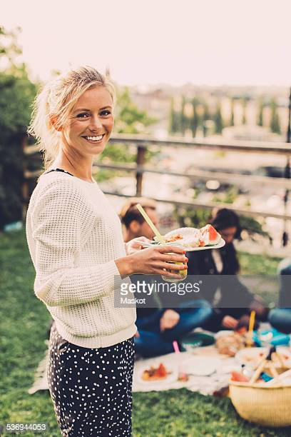 Side view portrait of happy woman holding breakfast at rooftop party