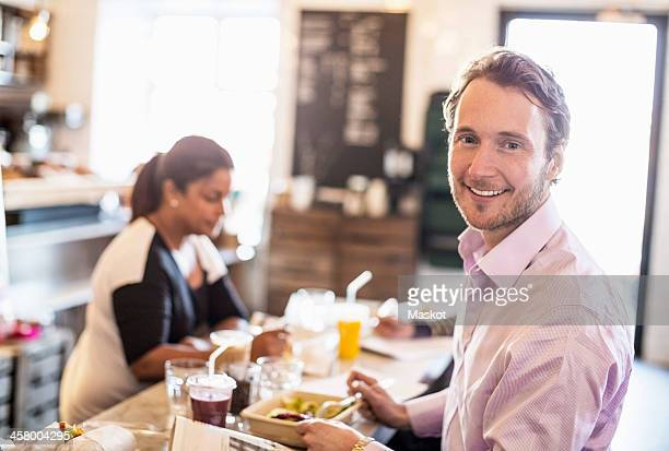Side view portrait of mid adult businessman having breakfast with colleague in background at office restaurant