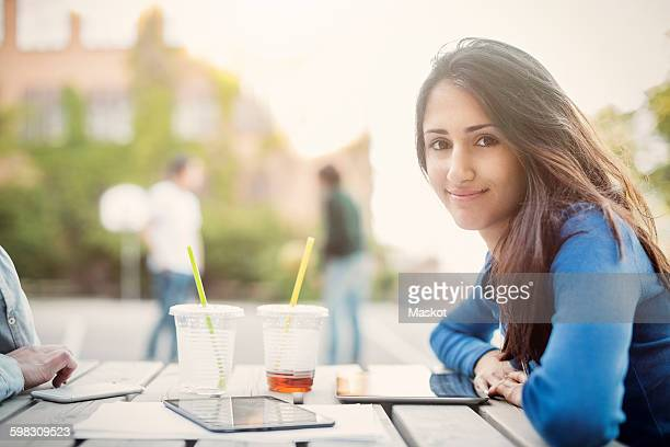 Side view portrait of smiling teenager sitting at table outdoors