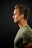 Side Profile Portrait against a Dark Background of a handsome muscular adult Caucasian male with a green t-shirt Cape Town South Africa