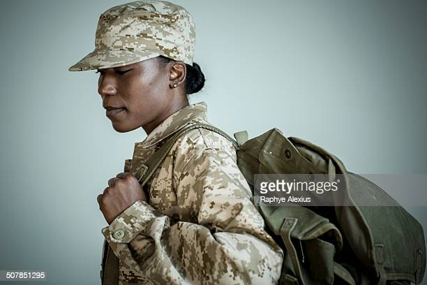 Side view studio portrait of female soldier with rucksack looking down