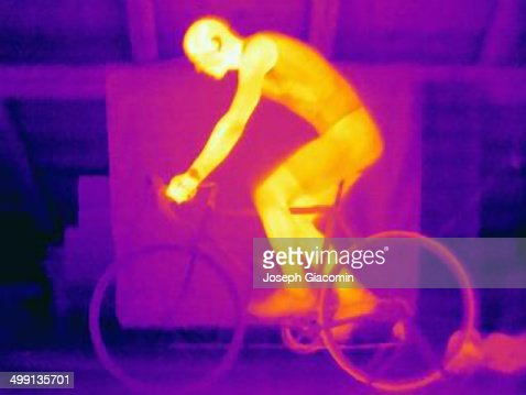Side view thermal image of young male cyclist in training, showing the heat of the muscles and of the bicycle tires