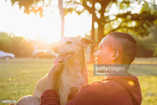 side view: young man hug his small Mixed-breed dog