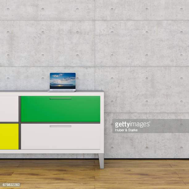 sideboard with laptop in front of concrete wall