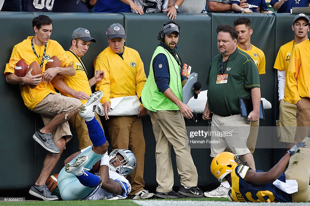 Sideline employees look on as Brice Butler #19 of the Dallas Cowboys falls out of bounds after scoring a second quarter touchdown against the Green Bay Packers during the second quarter at Lambeau Field on October 16, 2016 in Green Bay, Wisconsin.