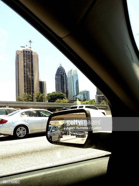 Side-View Mirror Of Car On Road In City