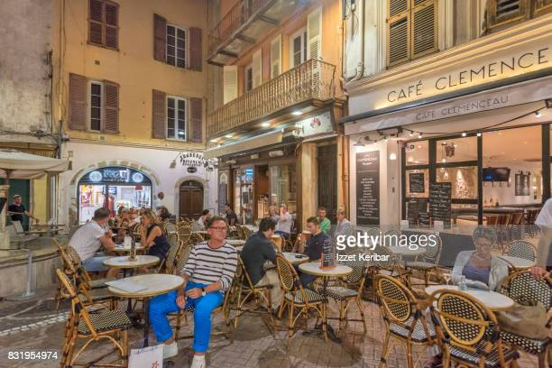 Sidewalk café and a few customers sitting there.  Antibes the old town. Alpes Maritimes, France
