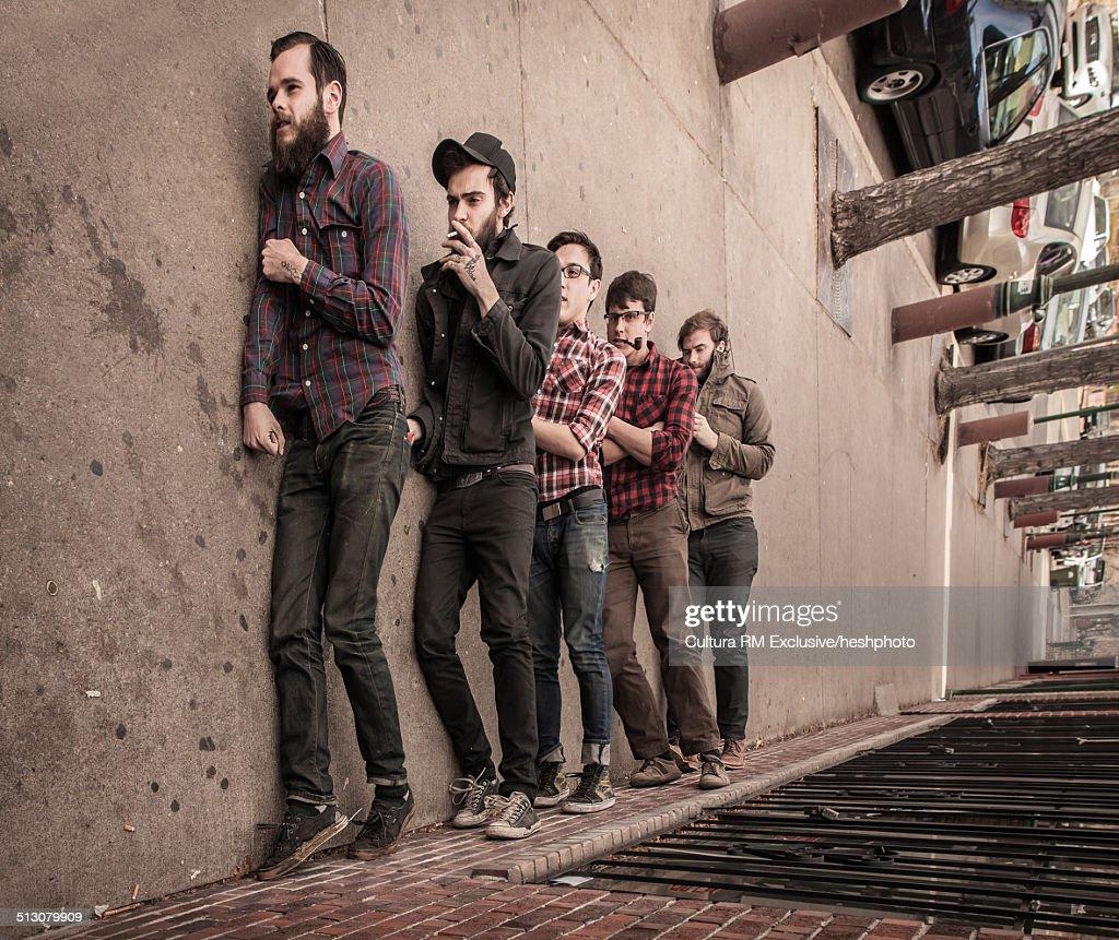 Sideway view of five young men pretending to walk along sidewalk