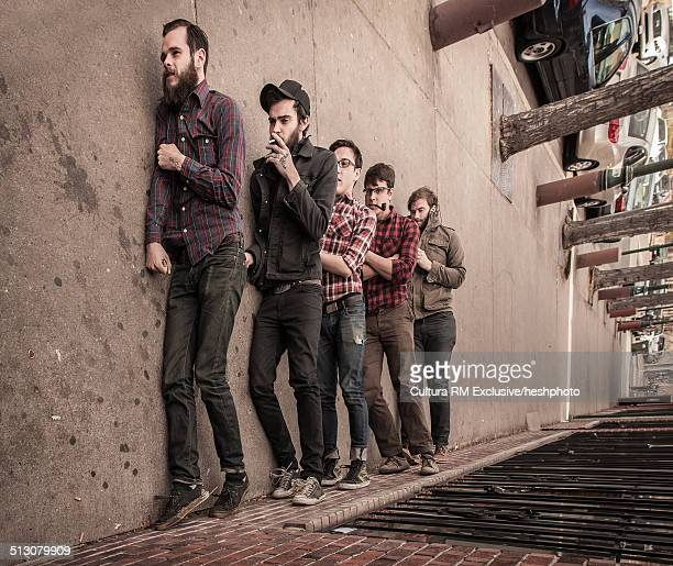 Sideway view of five young men pretending to walk along sidewalk