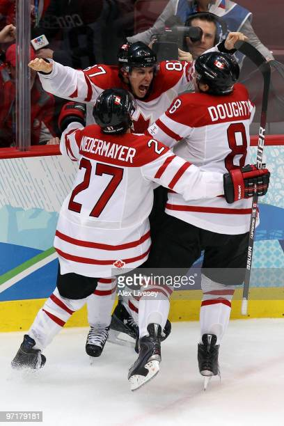Sidney Crosby of Canada celebrates with teammates Scott Niedermayer and Drew Doughty after scoring the matchwinning goal in overtime during the ice...
