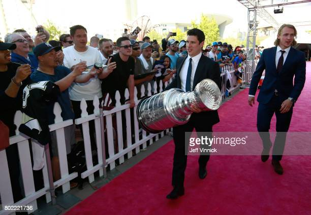 Sidney Crosby and Carl Hagelin of the Pittsburgh Penguins arrive with the Stanley Cup on the magenta carpet for the 2017 NHL Awards at TMobile Arena...