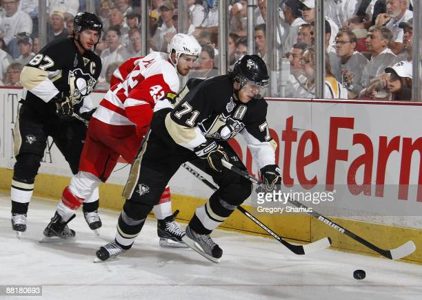 Sidney Crosby and Evgeni Malkin of the Pittsburgh Penguins double up against Darren Helm of the Detroit Red Wings during Game Three of the 2009 NHL...