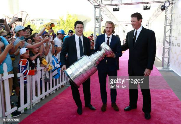 Sidney Crosby Carl Hagelin and coowner Mario Lemieux of the Pittsburgh Penguins arrive with the Stanley Cup on the magenta carpet for the 2017 NHL...