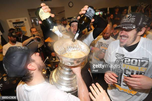 Sidney Crosby Nick Bonino and Evgeni Malkin of the Pittsburgh Penguins celebrate with the Stanley Cup in the locker room after Game Six of the 2017...