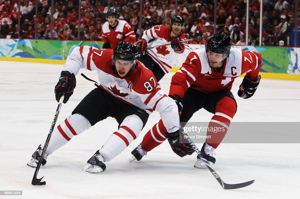 Sidney Crosby of Canada battles Mark Streit of Switzerland for the puck during the ice hockey men's preliminary game between Switzerland and Canada...