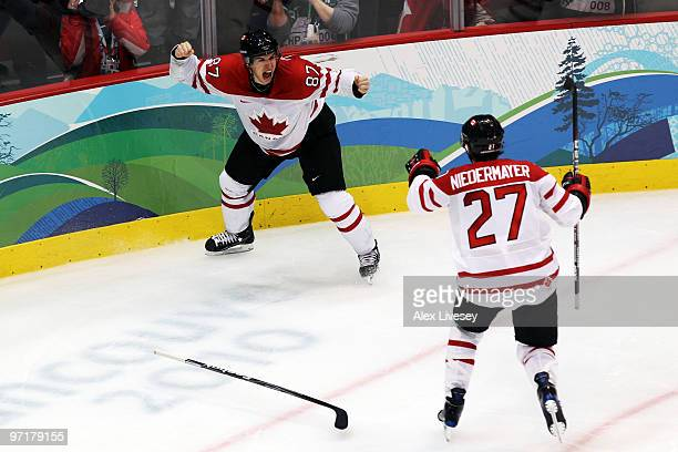 Sidney Crosby of Canada celebrates with his captain Scott Niedermayer after scoring the matchwinning goal in overtime past Ryan Miller of the United...
