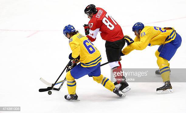 Sidney Crosby of Canada competes for the puck against Erik Karlsson and Alexander Edler of Sweden during the Men's Ice Hockey Gold Medal match on Day...