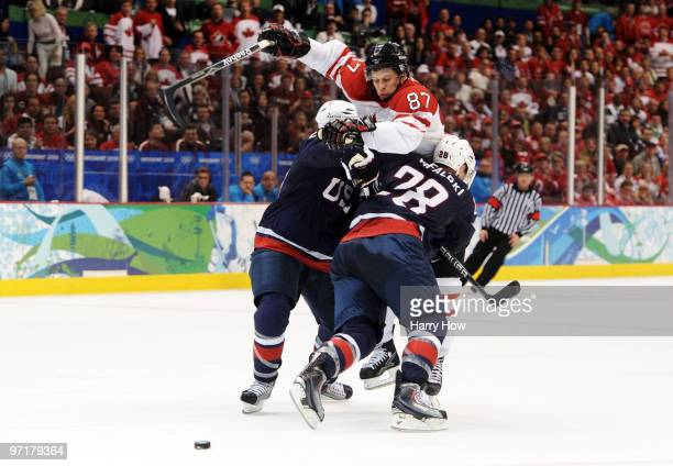 Sidney Crosby of Canada is checked by Brian Rafalski of the United States during the ice hockey men's gold medal game between USA and Canada on day...