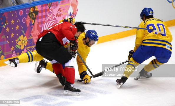 Sidney Crosby of Canada loses his helmet as he collides with Alexander Edler and Marcus Johansson of Sweden during the Men's Ice Hockey Gold Medal...