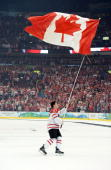 Sidney Crosby of Canada skates around the rink with the Canadian flag after the ice hockey men's gold medal game between USA and Canada on day 17 of...