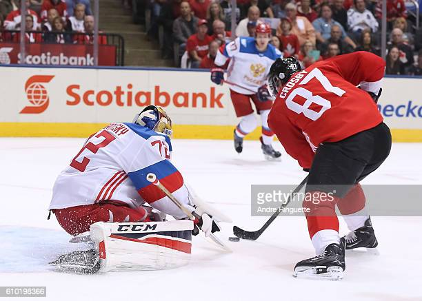 Sidney Crosby of Team Canada stickhandles the puck in on Sergei Bobrovsky of Team Russia to score a first period goal at the semifinal game during...