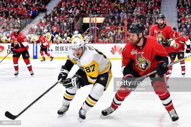 Sidney Crosby of the Pittsburgh Penguins and Marc Methot of the Ottawa Senators skate against each other in Game Four of the Eastern Conference Final...