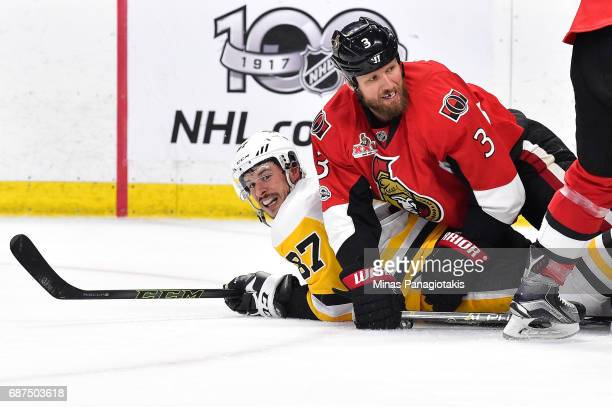 Sidney Crosby of the Pittsburgh Penguins and Marc Methot of the Ottawa Senators fall to the ice after colliding during the second period in Game Six...