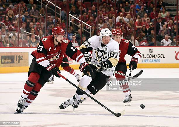 Sidney Crosby of the Pittsburgh Penguins and Oliver EkmanLarsson of the Arizona battle for a loose puck as Michael Stone of the Coyotes trails the...