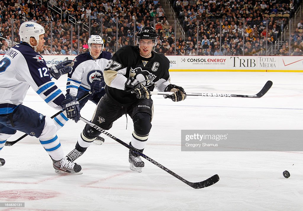 Sidney Crosby #87 of the Pittsburgh Penguins and Olli Jokinen #12 of the Winnipeg Jets skates for the loose puck on March 28, 2013 at Consol Energy Center in Pittsburgh, Pennsylvania.