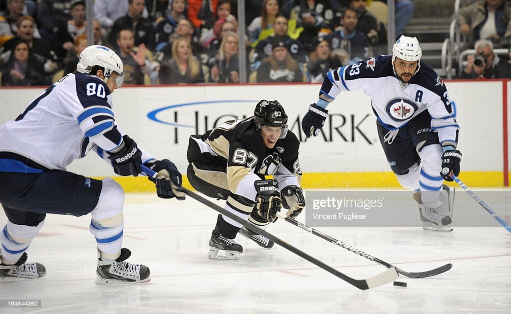 Sidney Crosby #87 of the Pittsburgh Penguins attempts to get between Nik Antropov #80 and Dustin Byfuglien #33 of the Winnipeg Jets during the third period on February 28, 2013 at the CONSOL Energy Center in Pittsburgh, Pennsylvania.
