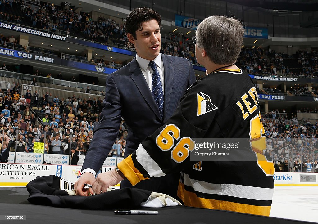 Sidney Crosby #87 of the Pittsburgh Penguins autographs a fans jersey as part of fan appreciation night after the game against the Carolina Hurricanes on April 27, 2013 at Consol Energy Center in Pittsburgh, Pennsylvania.