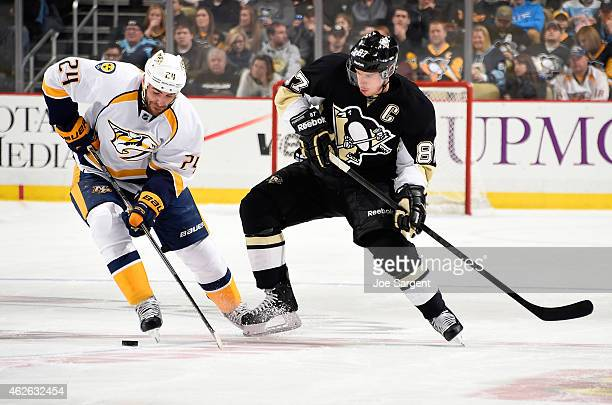 Sidney Crosby of the Pittsburgh Penguins battles for the loose puck against Eric Nystrom of the Nashville Predators at Consol Energy Center on...