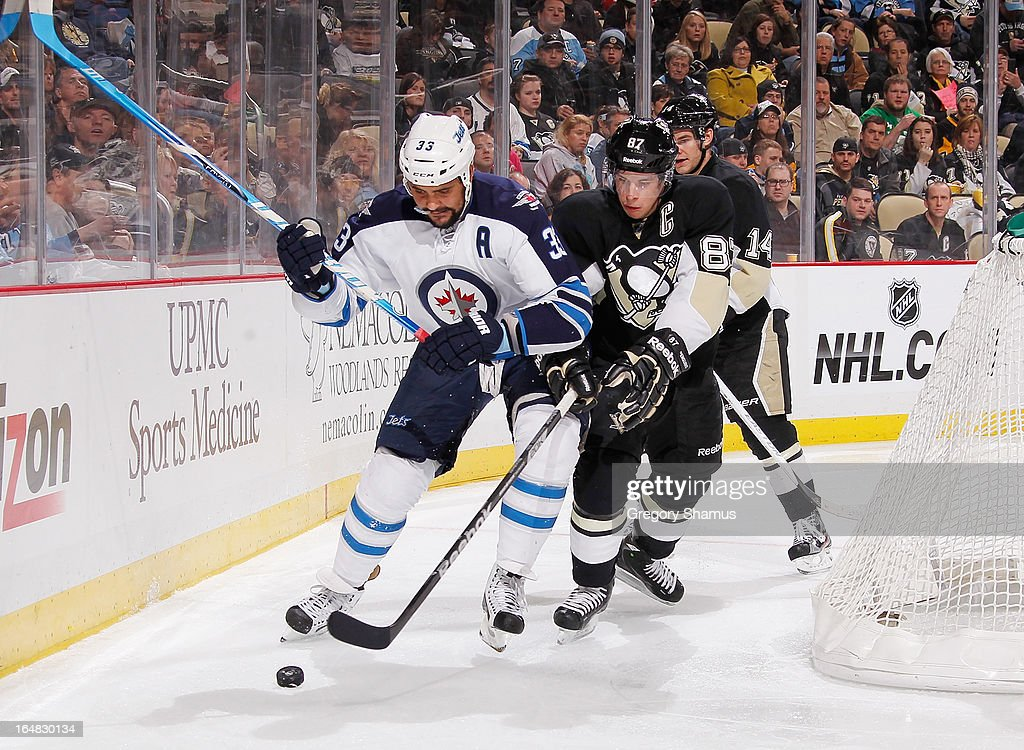Sidney Crosby #87 of the Pittsburgh Penguins battles for the puck against Dustin Byfuglien #33 of the Winnipeg Jets on March 28, 2013 at Consol Energy Center in Pittsburgh, Pennsylvania.