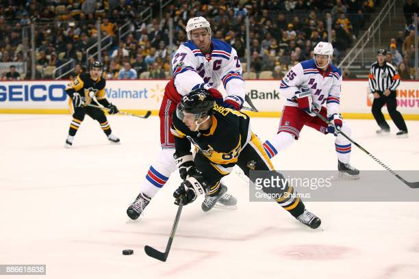 Sidney Crosby of the Pittsburgh Penguins battles for the puck with Ryan McDonagh of the New York Rangers during the second period at PPG PAINTS Arena...