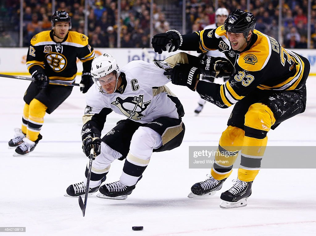<a gi-track='captionPersonalityLinkClicked' href=/galleries/search?phrase=Sidney+Crosby&family=editorial&specificpeople=212781 ng-click='$event.stopPropagation()'>Sidney Crosby</a> #87 of the Pittsburgh Penguins carries the puck in front of a stickless <a gi-track='captionPersonalityLinkClicked' href=/galleries/search?phrase=Zdeno+Chara&family=editorial&specificpeople=203177 ng-click='$event.stopPropagation()'>Zdeno Chara</a> #33 of the Boston Bruins in the second period during the game at TD Garden on December 7, 2013 in Boston, Massachusetts.