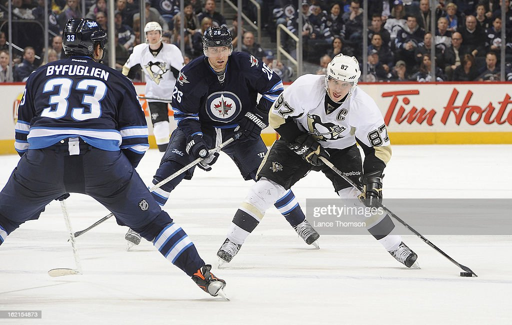 Sidney Crosby #87 of the Pittsburgh Penguins carries the puck up the ice as Dustin Byfuglien #33 of the Winnipeg Jets defends during third period action at the MTS Centre on February 15, 2013 in Winnipeg, Manitoba, Canada. The Penguins defeated the Jets 3-1.